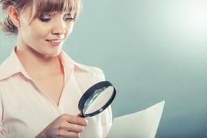 Femme lisant un document avec une loupe